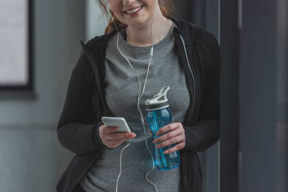 Curvy girl with water bottle listening to music in gym