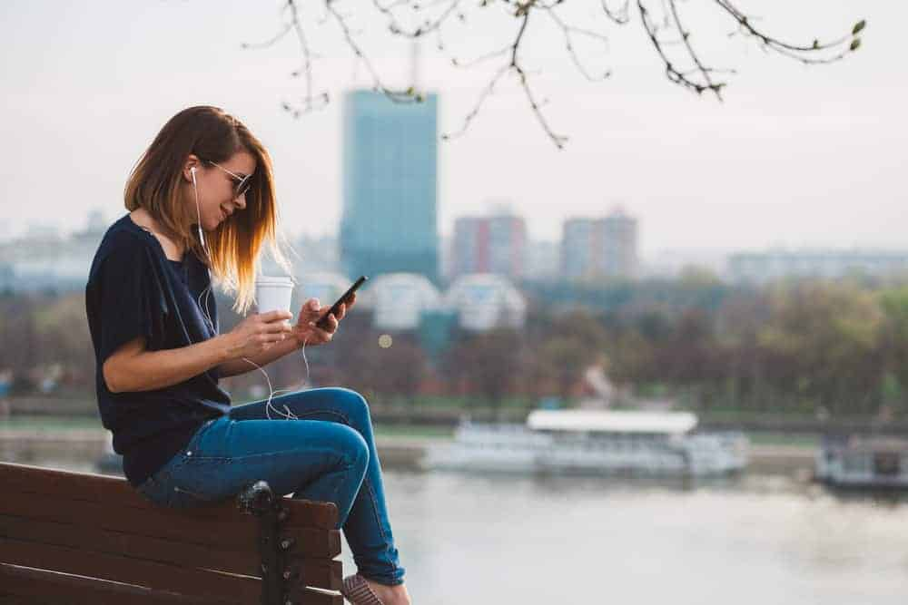 Young woman enjoying music on the smartphone in the park