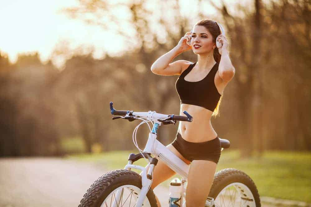 Sports girl holds a bluetooth headphones in her hands and sits on a bicycle at sunset in the park