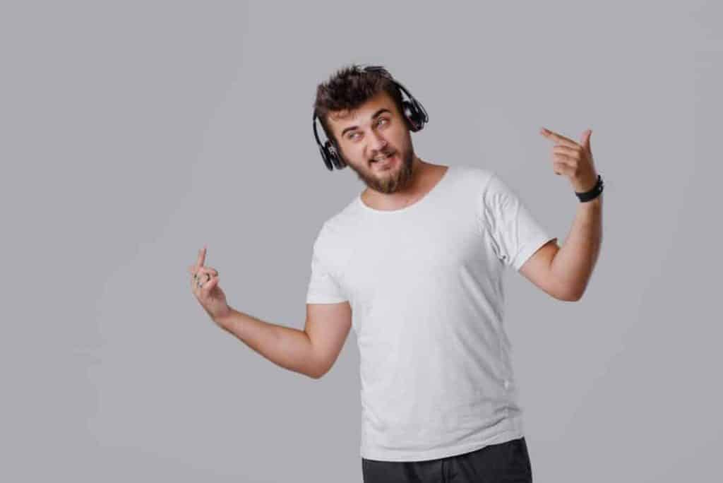 A young man with a beard listens to loud music in wireless headphones. He does not like these sounds