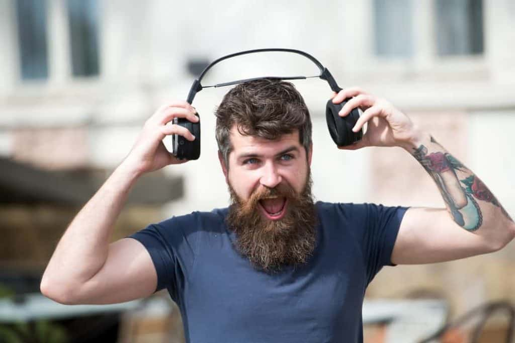 Man with long beard and mustache puts wireless headphones on head, defocused urban background. Hipster with headphones on shouting face listening music while walking. Music lover concept
