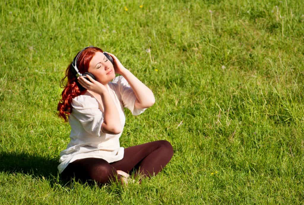beautiful redhead young woman listening to music with headphones