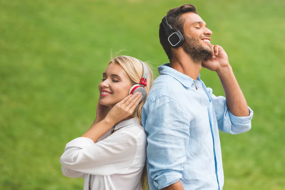 Side view of smiling couple in headphones standing back to back and listening music in closed back headphones under 200$