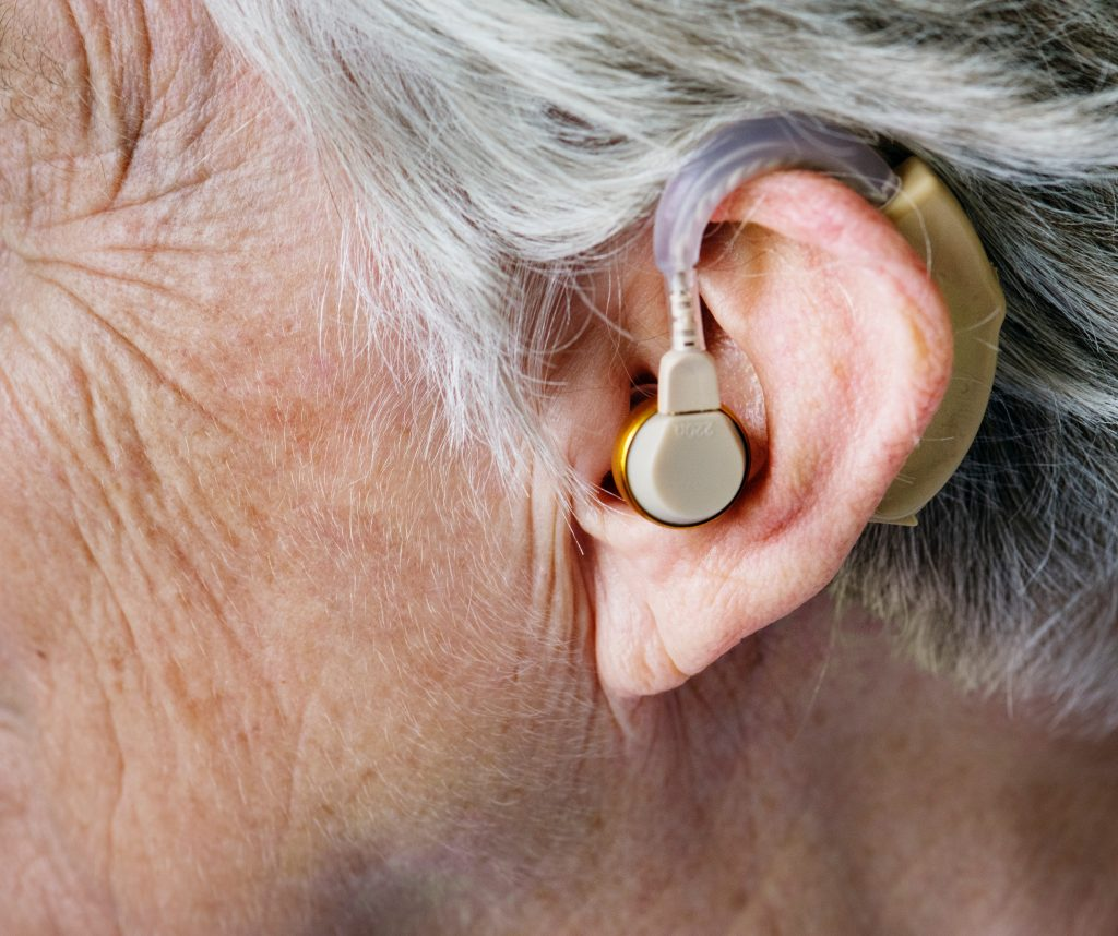 an image for the best headphones for hearing Impaired - old man wearing his hearing aids