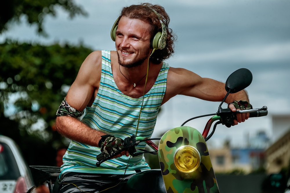 Modern hipster man with military headphones on motobike