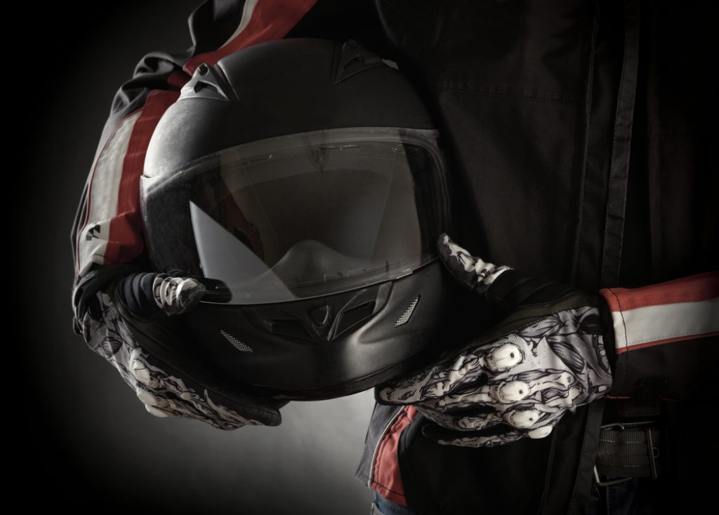 Motorcyclist with helmet and an earbuds in his hands